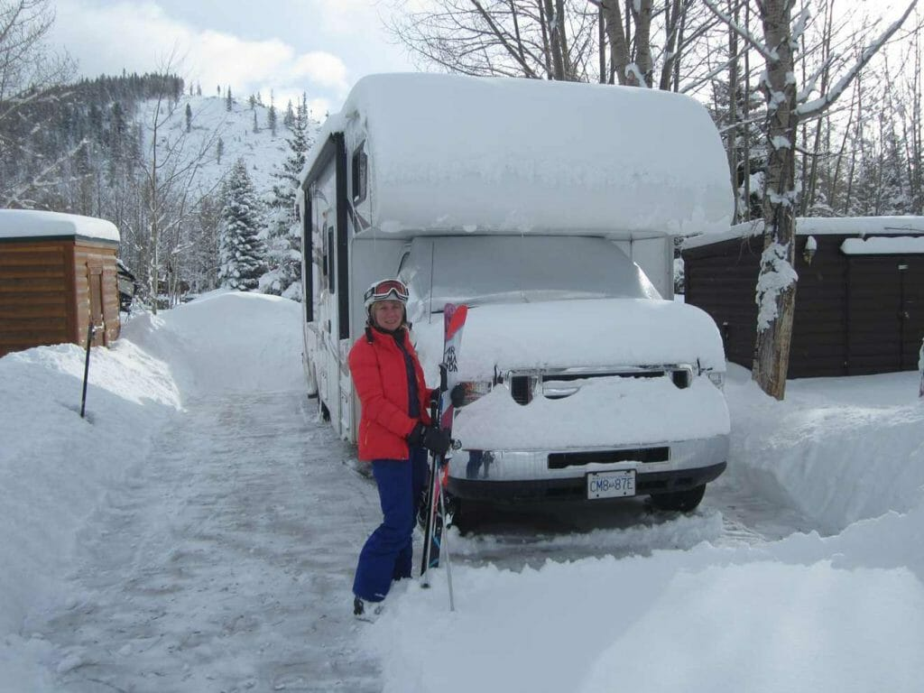 Standing outside the RV with skis