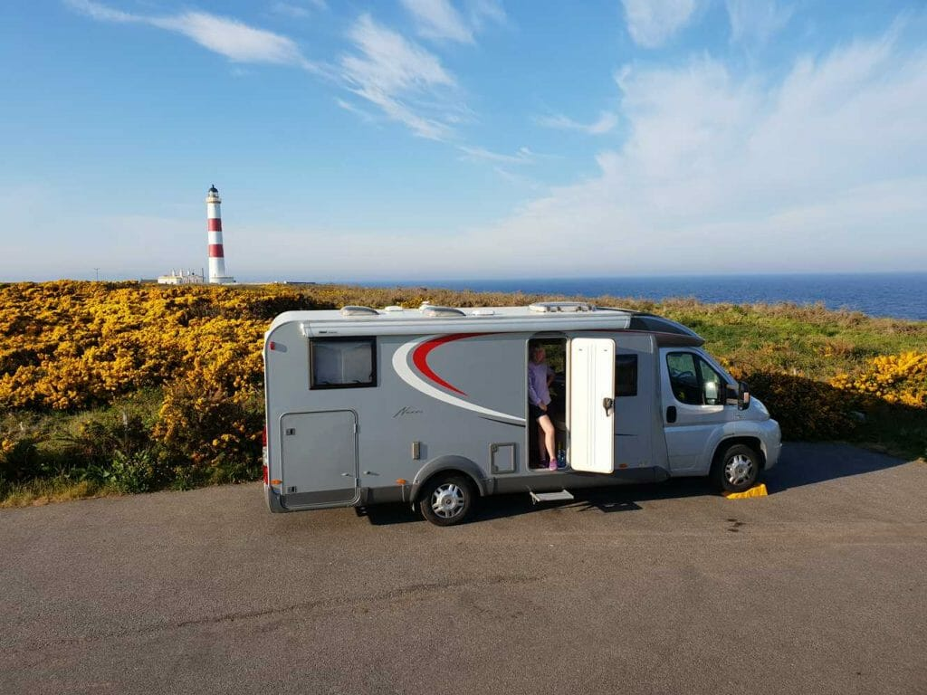 Our motorhome with lighthouse in background on our Scottish road trip