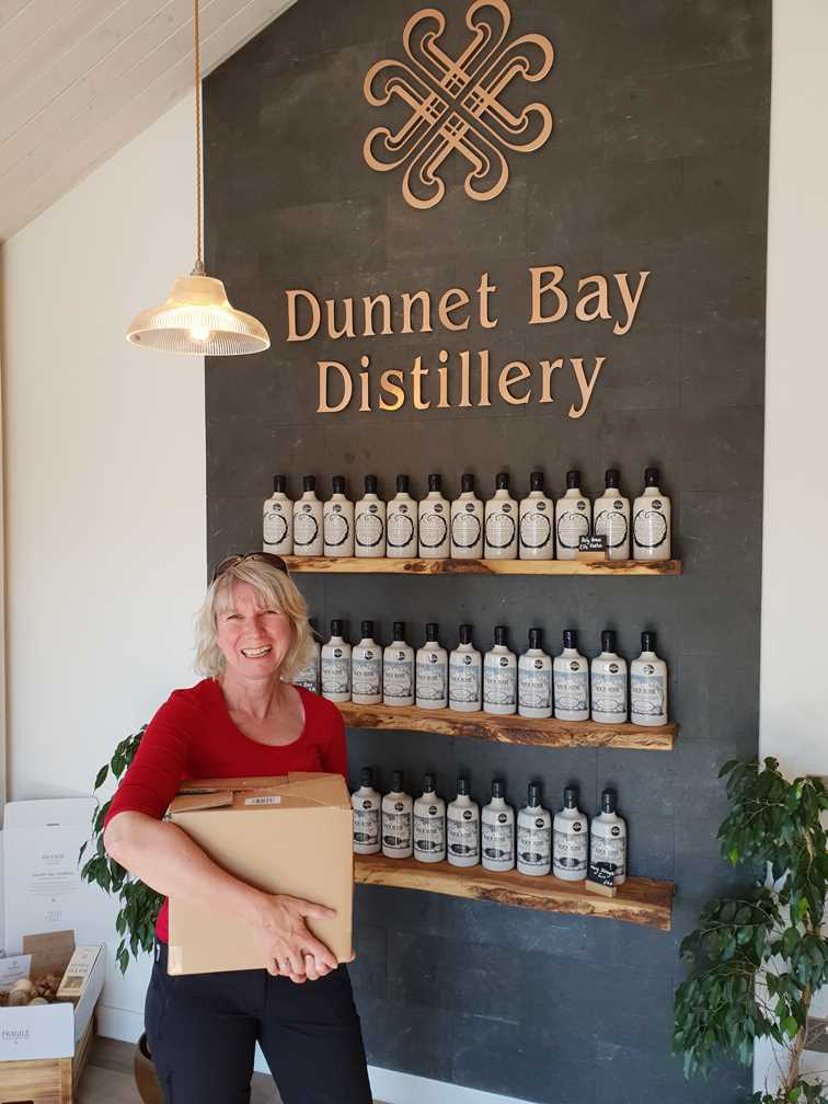 Me holding a box of gin outside the Dunnet Bay gin distillery