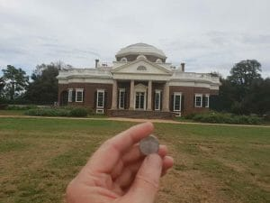 holding a nickle with a picture of Montello engraved on it with the house in the background