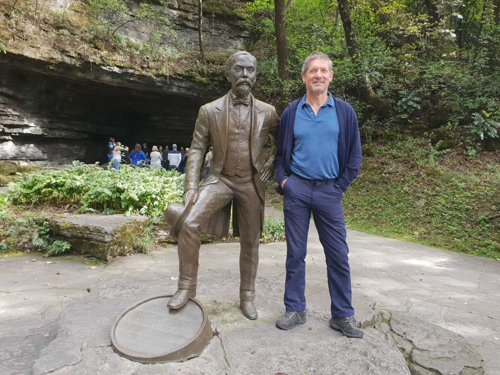 Peter standing with statue of Jack Daniel