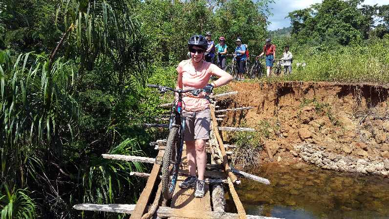 Jane crossing bridge with bike